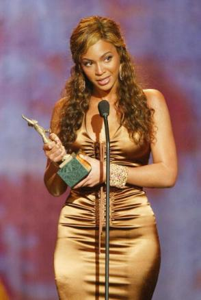 "LOS ANGELES, CA - MARCH 20: Singer Beyonce receives the 2004 Sammy Davis Jr. Award for ""Entertainer of the Year"" at the ""18th Annual Soul Train Music Awards"" at the Scottish Rite Auditorium on March 20, 2004 in Los Angeles, California. (Photo by Kevin Winter/Getty Images)"